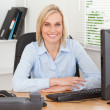 Stock Photo: Smiling woman sitting behind a desk