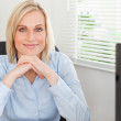 Cute blonde woman with chin on her hands behind a desk — Stock Photo #11181700