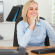 Smiling woman with chin on hand behind a desk looking at screen — Stock Photo