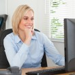 Smiling blonde woman with chin on hand behind a desk looking at — Stock Photo