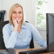 Ute blonde woman with chin on hand behind a desk looking at scre — Stock Photo #11181711