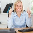 Young woman sitting behind desk with thumbs up — Stock Photo #11181712