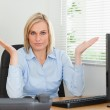 Serious woman sitting behind desk not having a clue what to do n — Stock Photo #11181722