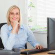 Working smiling woman in front of a screen looking into camera — Stock Photo