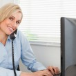 Charming blonde businesswoman on the phone while typing looks in — Stock Photo