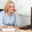 Cute blonde businesswoman on mobile writing something down looks — Stock Photo