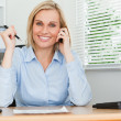 Portrait of a businesswoman smiling into camera with pen in hand — Stock Photo