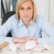 Sad woman sitting in front of an shattered piggy bank with less — Stock Photo