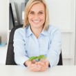 Woman holding a little plant smiies into camera — Stock Photo