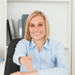 Smiling blonde businesswoman giving hand — Stock Photo