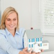 Smiling businesswoman showing model house — Stock Photo #11182002