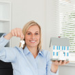Gorgeous blonde businesswoman showing model house and keys looks — Stock Photo #11182015