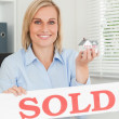 Gorgeous blonde businesswoman showing miniature house and SOLD s — Stock Photo