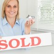 Blonde businesswoman showing miniature house and SOLD sign looki — Stock Photo