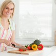 Cute woman cutting red pepper looks into camera — Stock Photo