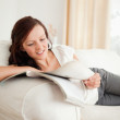 Young red-haired woman studying on the sofa - Stock Photo