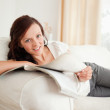 Young red-haired woman studying on the sofa looking into the cam - Stock Photo