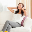 Cute woman relaxing on a sofa listening to music — Stock Photo