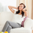 Gorgeous red-haired woman relaxing on a sofa listening to music — Stock Photo