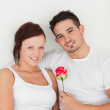 Happy couple with a rose looking at the camera — Stock Photo