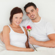 Happy couple in a bed with a rose — Stock Photo