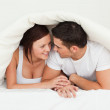Stock Photo: Happy couple hiding under blanket