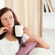 Thoughtful woman holding a cup - Stock Photo