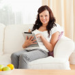 Young woman with a tablet sitting on a sofa - Stock Photo