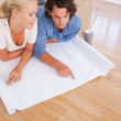 Young couple looking at their future room on a plan — Stock Photo #11183891