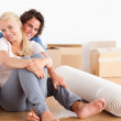 Happy couple sitting on the floor — Stock Photo #11184016