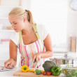 Blonde woman using a tablet computer to cook — Stock Photo