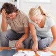 Despaired couple calculating their expenses — 图库照片