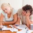 Unhappy couple listing expenses — Stock Photo #11184850