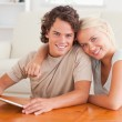 Hugging cute couple with a tablet — Stock Photo
