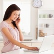 Woman telephoning and typing — Stock Photo