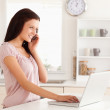 Stock Photo: Woman Telephoning and typing on laptop