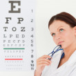 Female opticiwith eye test in office — Stock Photo #11185093