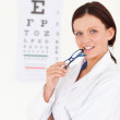 Gorgeous female optician with an eye test — Stock Photo #11185097