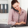 Stock Photo: Businesswomtelephoning and typing