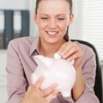 podnikatelka dát peníze v bance prasátko — Stock fotografie