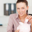 Businesswoman putting 10 euro in piggy bank — Stock Photo