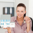 Businesswoman shows keys and model house — Stock Photo