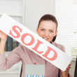 Businesswoman holding sold sign - Stock Photo