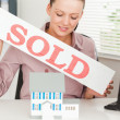 Businesswoman holding a sold sing — Stockfoto