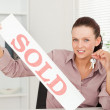 Businesswoman holding keys and sold sign — Stock Photo #11185283