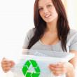 Gorgeous woman holding a recycling box - Stock Photo