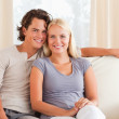 Smiling couple sitting on a sofa — Stock Photo #11185593