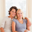 Portrait of a young couple sitting on a sofa — Stock Photo