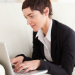 Charming businesswoman lying on a sofa with a laptop — Stock Photo