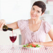 Stock Photo: Wompouring redwine in glass